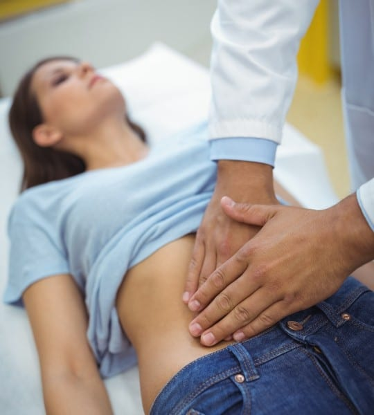 doctor examining the stomach of 2 showing the concept of Home