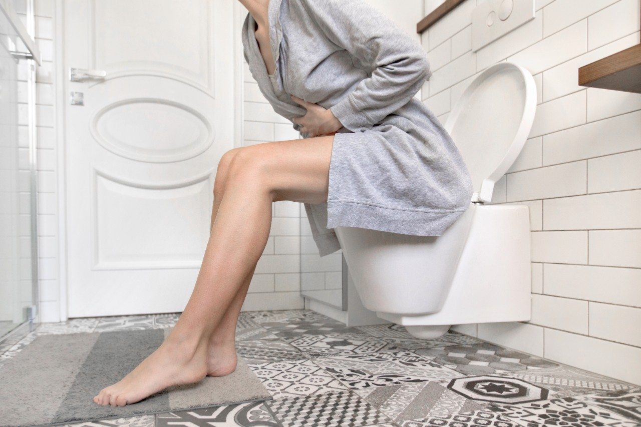 woman with bladder pain sitting on a toilet
