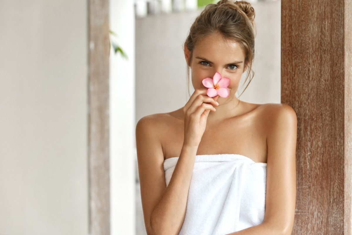 woman holding a flower in front of her face