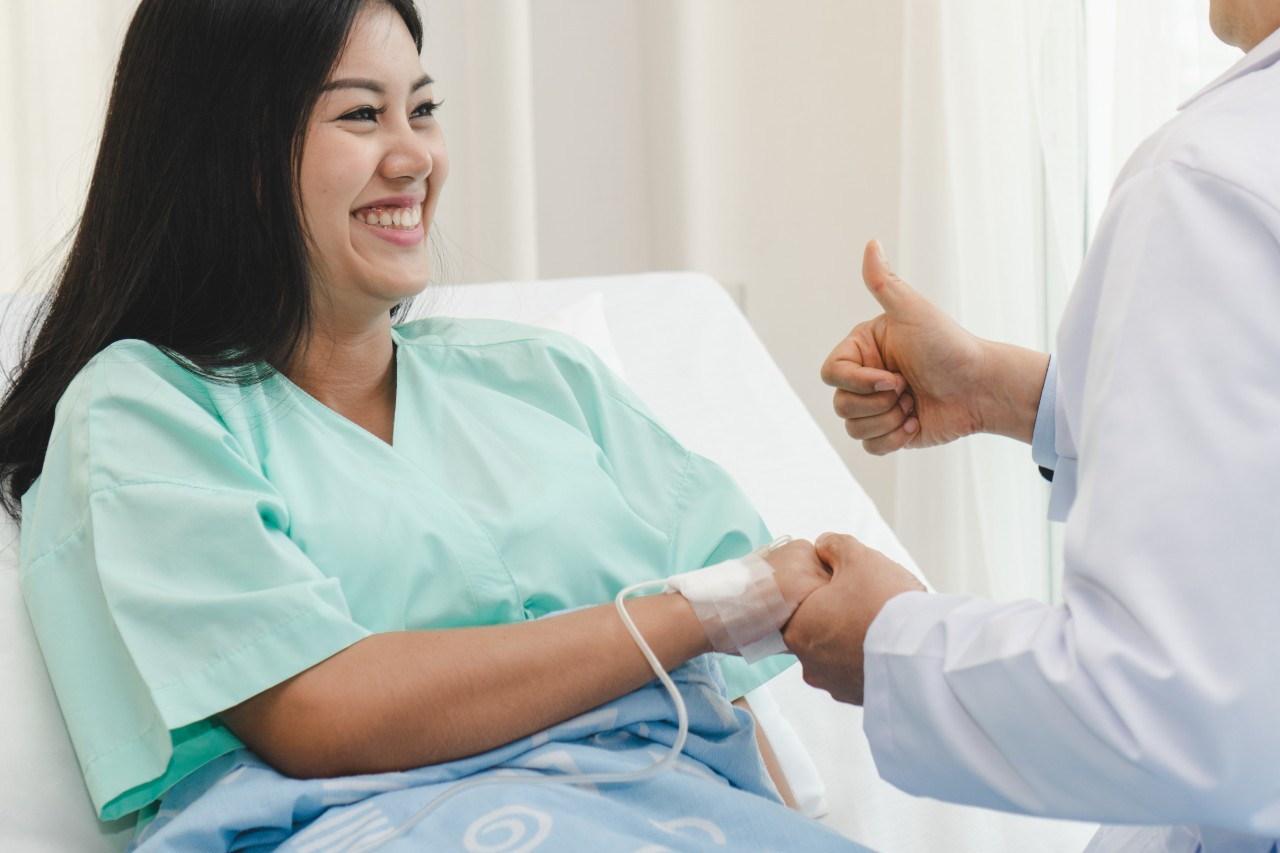 woman sitting in a hospital bed holding a doctor's hand