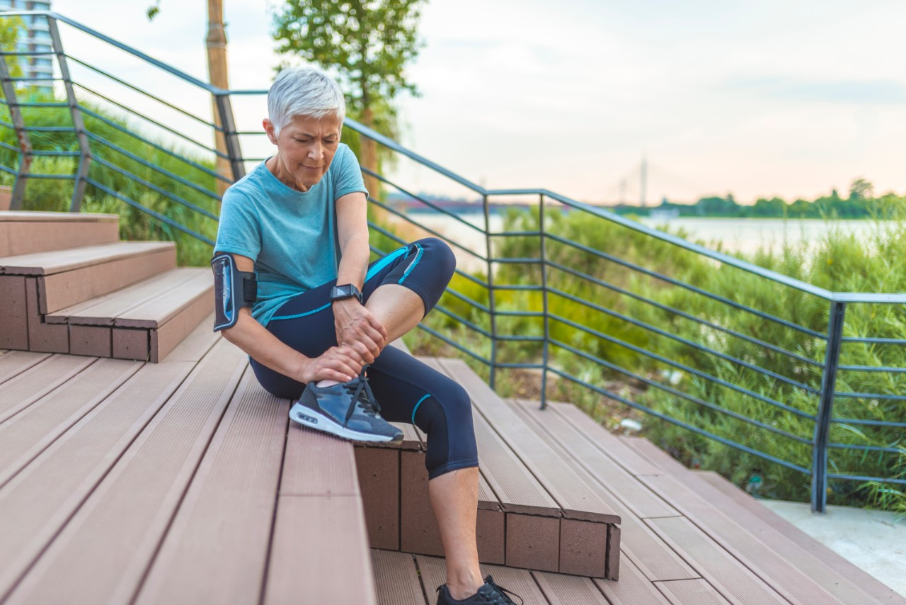 woman sitting on steps checking her ankle